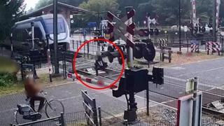 Salva per un soffio: attraversa i binari con il treno in arrivo