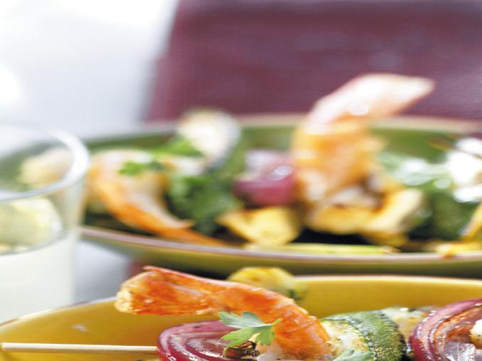 Spiedini di gamberoni, cipolle e zucchine su carciofi