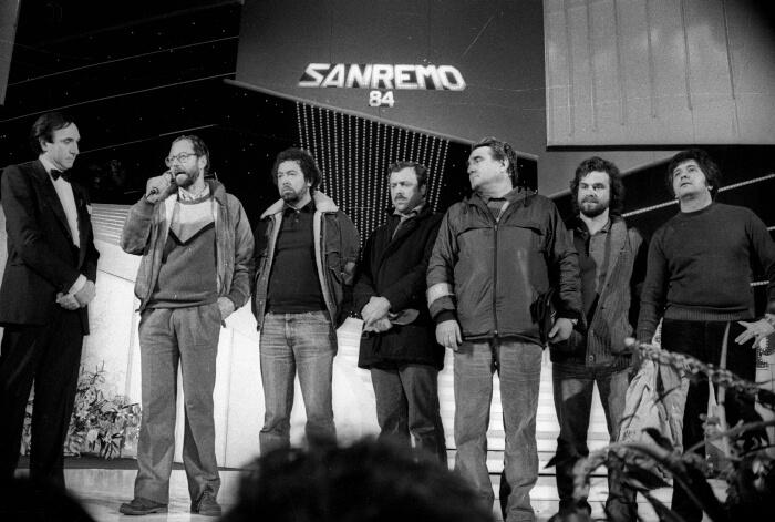 1984 - Pippo Baudo sul palco insieme a una delegazione dei 2000 metalmeccanici dell'Italsider che manifestavano davanti al Teatro Ariston contro la minaccia della chiusura dello stabilimento di Genova (Ansa)