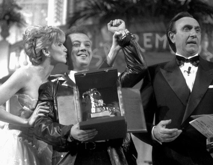 """1993 - Enrico Ruggeri premiato da Pippo Baudo e Lorella Cuccarini per il brano """"Mistero"""" (Ap/Bruno)"""
