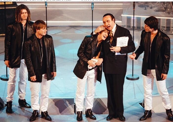 1996 - Pippo Baudo con i Take That (già senza Robbie Williams) sul palco di Sanremo (Ansa)